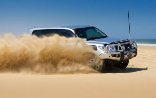 LC200 Series on beach tearing up sand with Octagon rims