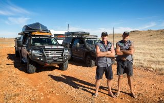 Jase and Simon from All 4 Adventure on road in front of their vehicles