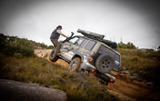 Offroad Adventure Show Holden wheels on Jackaroo with Jamie standing on side of 4WD stuck in mud